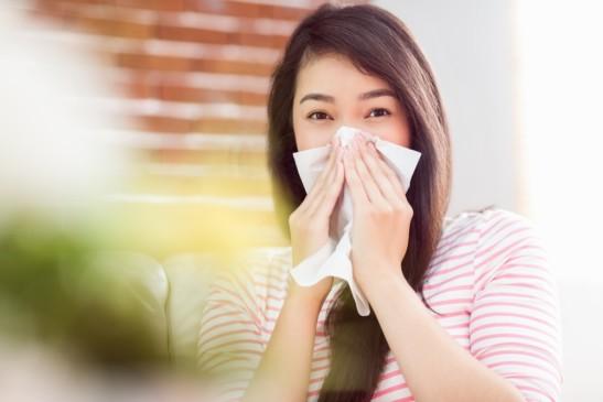 Mujer sentada en sillón con un pañuelo desechable sonándose la nariz