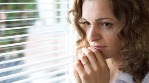 Mujer con ansiedad frente a la ventana