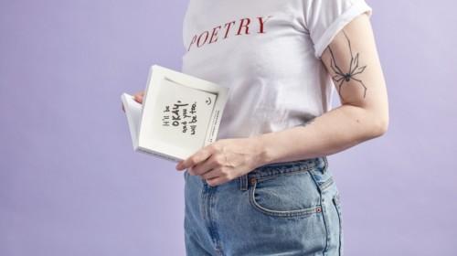 chica joven tomando un libro de poesía entre sus manos