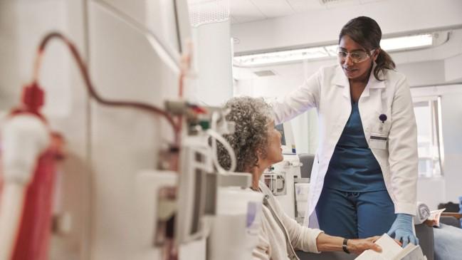 Mujer sentada con enfermera al lado recibiendo tratamiento para enfermedad renal