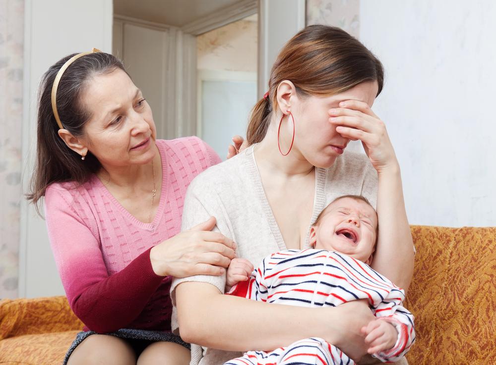 madre de familia cargando a su recién nacido en brazos llorando