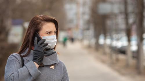 Mujer que lleva máscara médica protectora una calle vacía, al aire libre. Mujer que tiene un teléfono. Concepto de autoasistencia