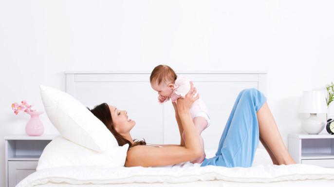 Mamá feliz acostada en el sillón alzando a su bebé en brazos