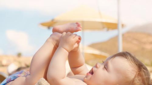 Bebé en la playa tomando rayos de sol