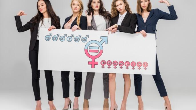 Jóvenes empresarias con gran cartel con el símbolo de la igualdad