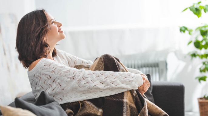 mujer contenta sentada en sofá