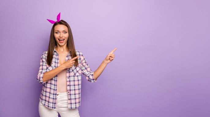 Retrato de la joven hipster sonriente con camiseta rosa
