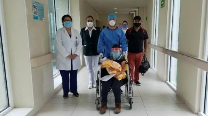 Paciente y médicos recorriendo pasillo