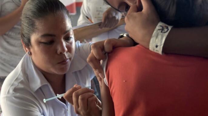Enfermera vacunando a menor