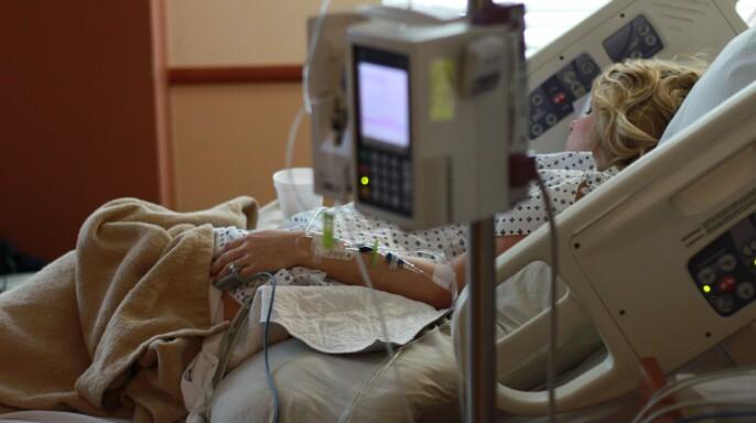 Mujer en cama de hospital.