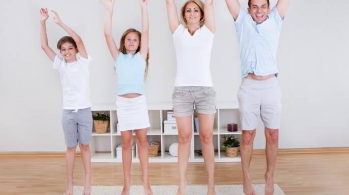 Familia haciendo ejercicios de estiramiento en la alfombra