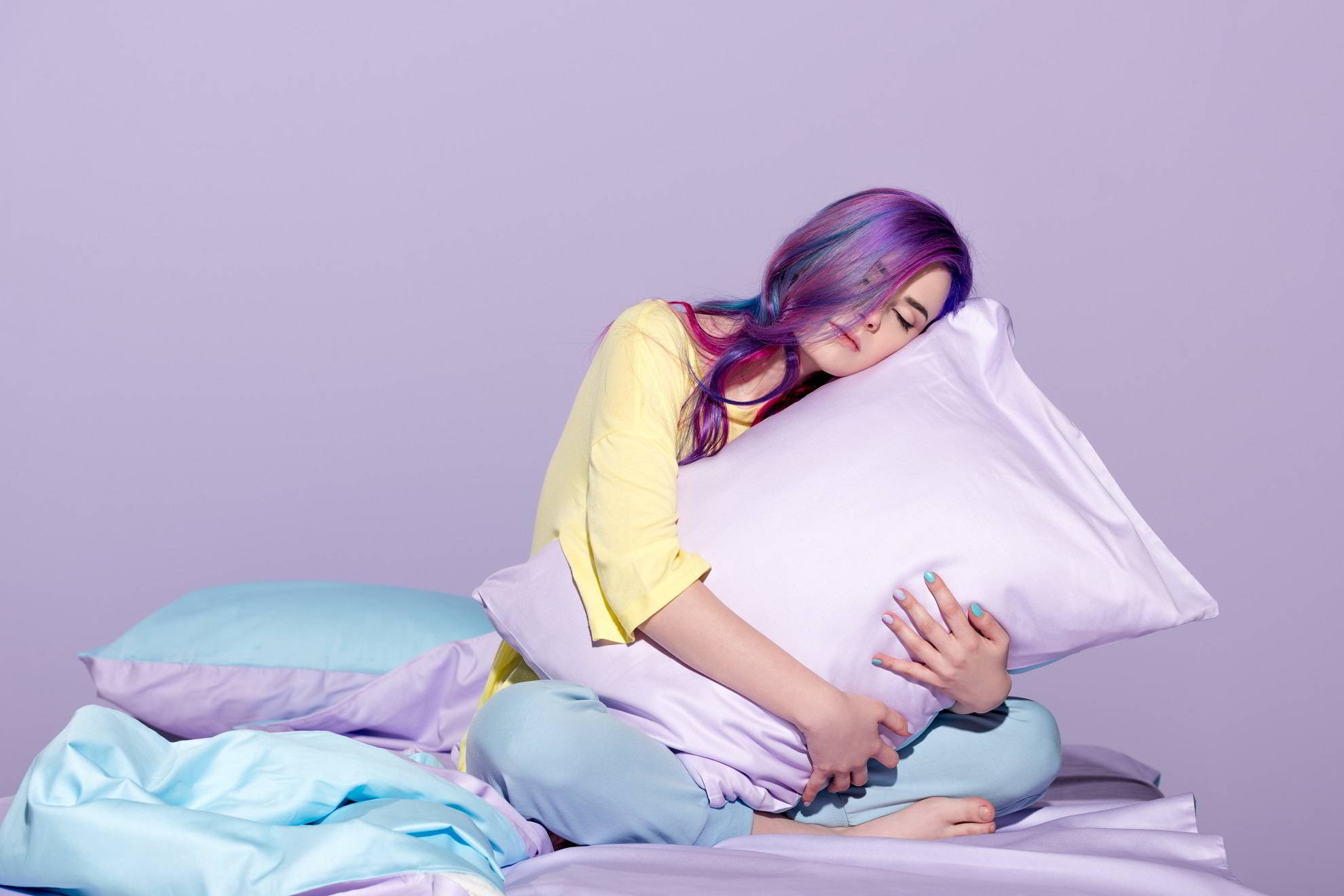 joven sentada en la cama y abrazando una almohada