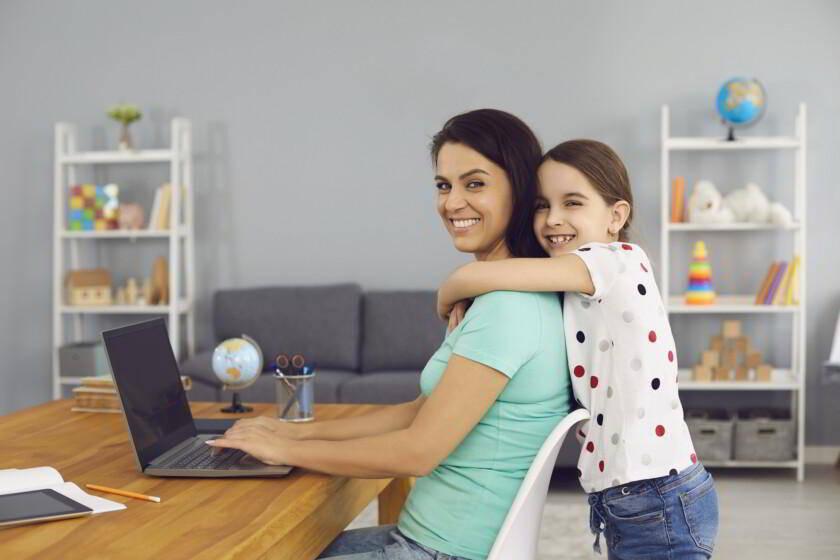 Hija abrazando a su mamá mientras trabaja en línea