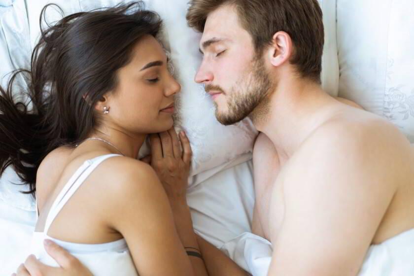 pareja feliz se encuentran juntos en la cama