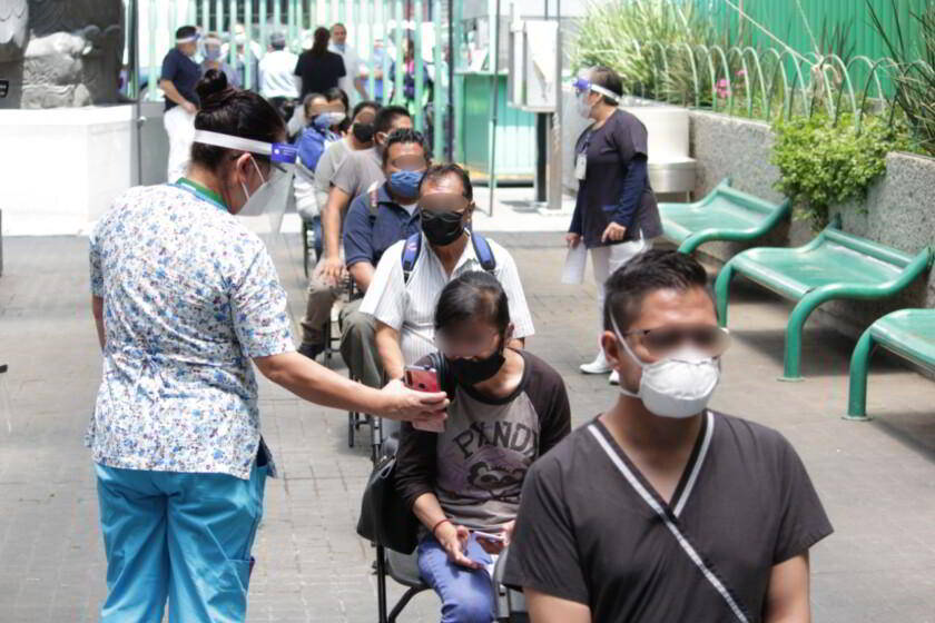 Pacientes en una fila con una especialista mostrando un dispositivo móvil