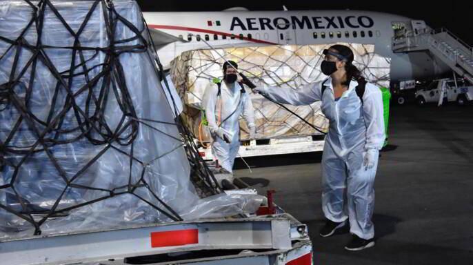 Personal con aspersores desinfectando contenedor al fondo un avión