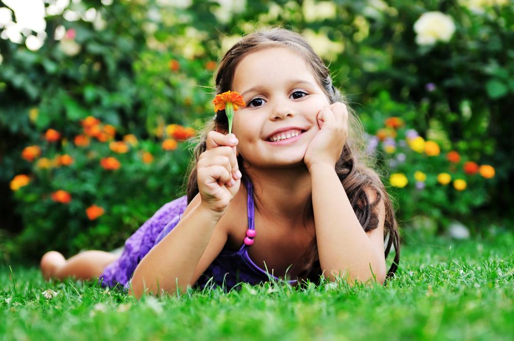 niña sonriente con flor en la mano