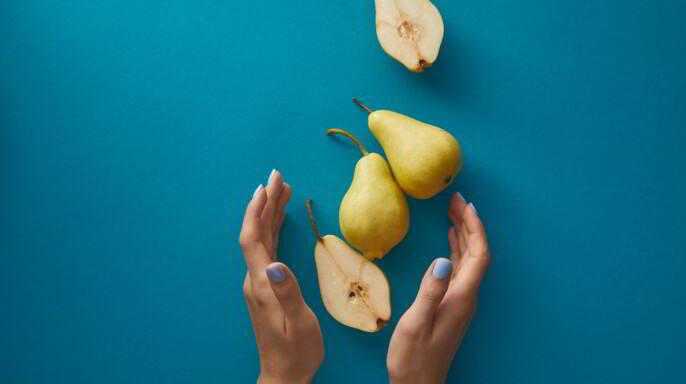 manos de mujer junto a peras