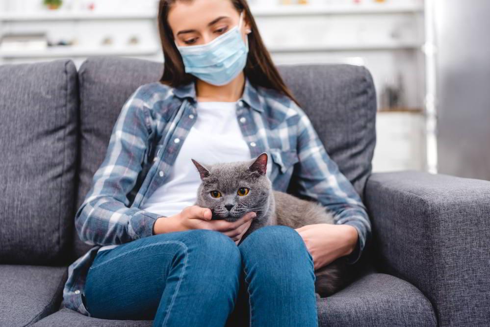 mujer joven con cubrebocas y gato