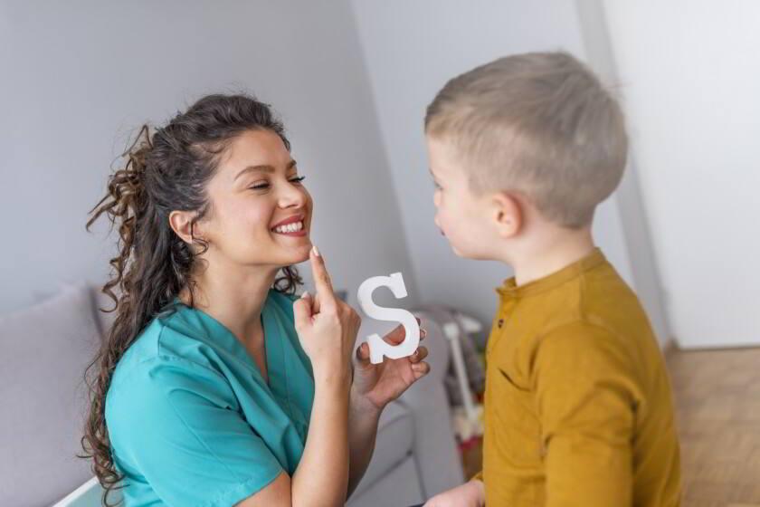 Logopeda enseñando a niño a decir letra S