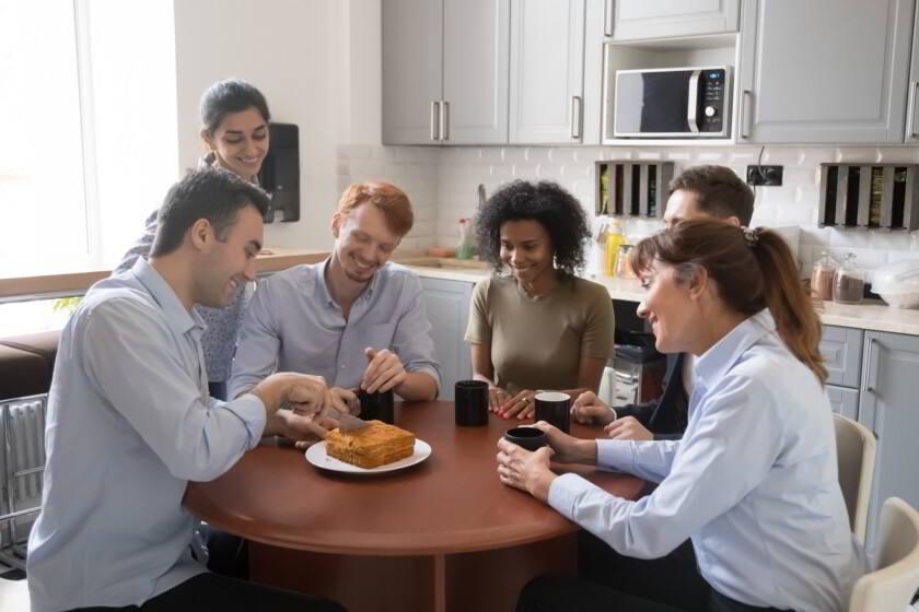 personas en una oficina comiendo un pastel casero