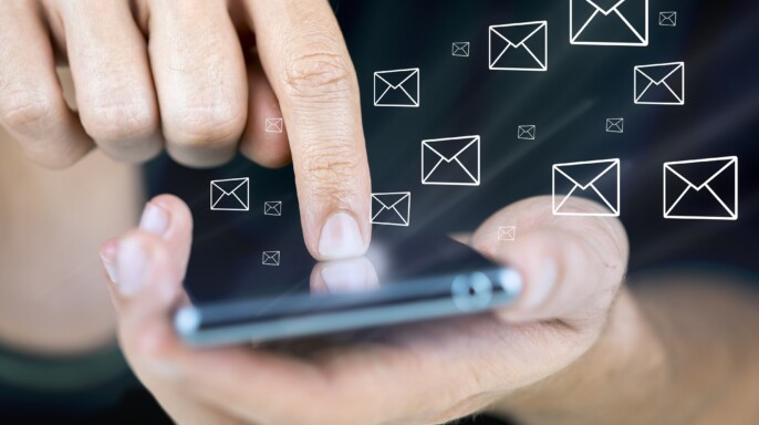 Acercamiento a una mano con teléfono móvil en la mano e iconos de mensajes