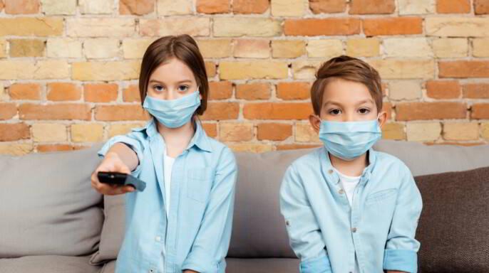 Niños con cobrebocas jugando videojuegos