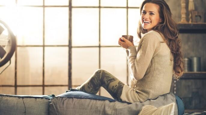 mujer sonriente mirando sobre el hombro sosteniendo una copa