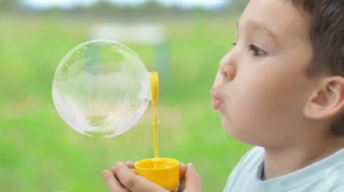 Niño jugando con buebujas