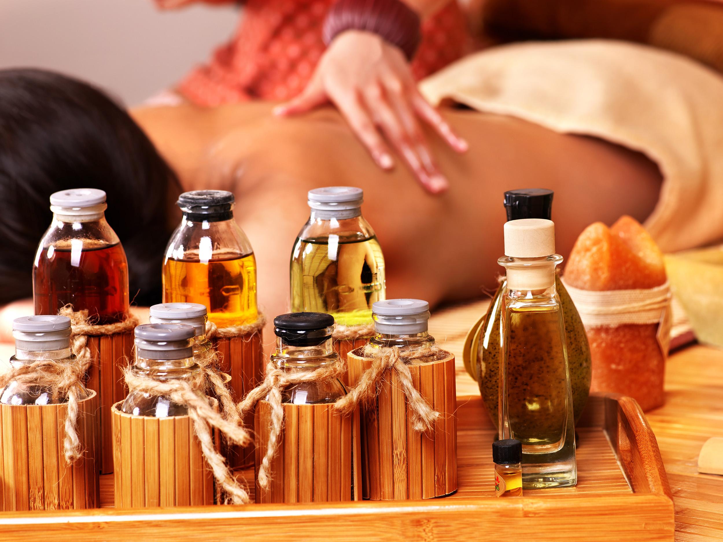Mujer recibiendo masaje en spa de bambú con aceites esenciales..