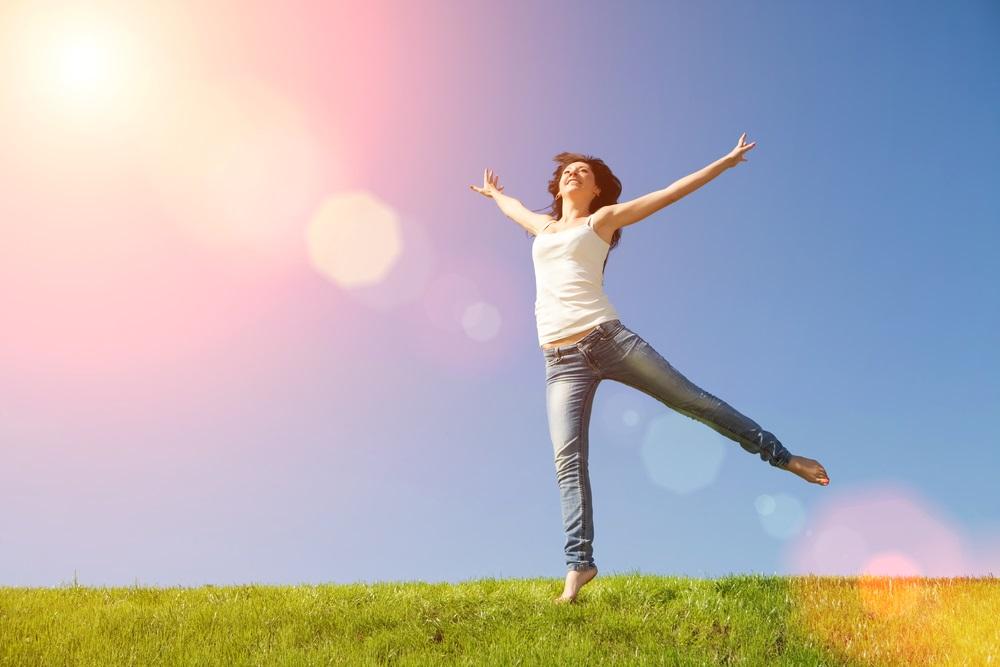 mujer feliz bajo los rayos del sol