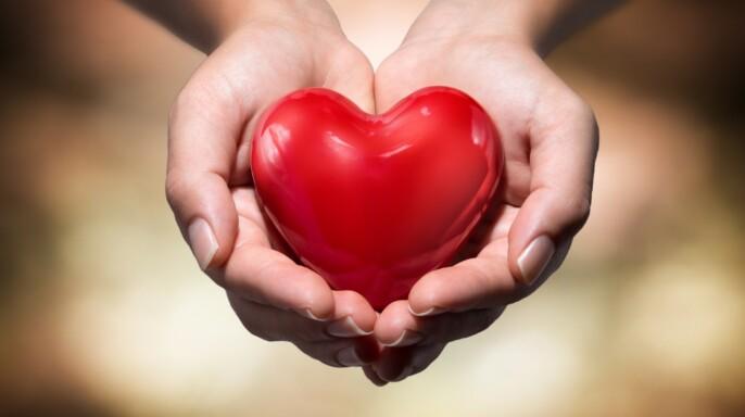 Niña con brazos extendidos ofreciendo una figura en forma de corazón
