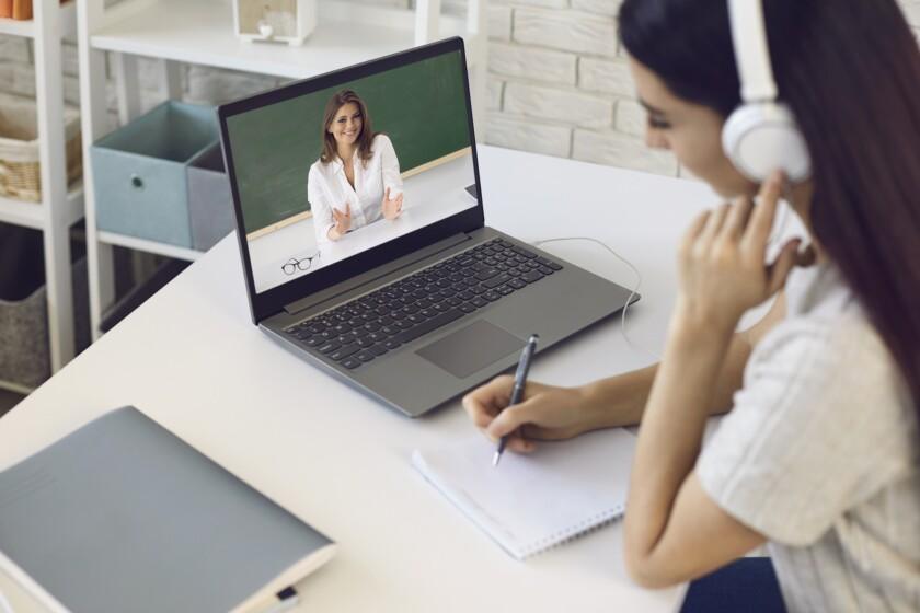 Profesor en línea. Estudiante con auriculares escucha video