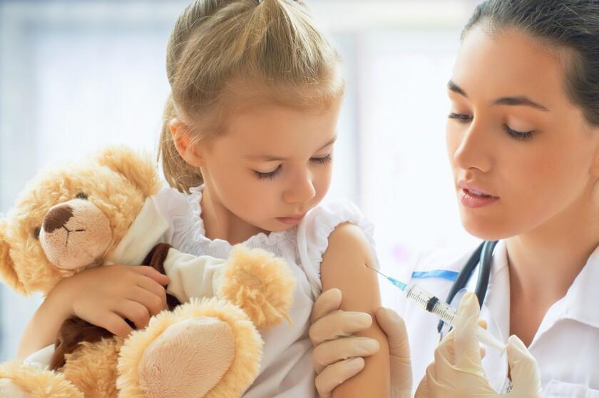Pediatra vacunando a niña