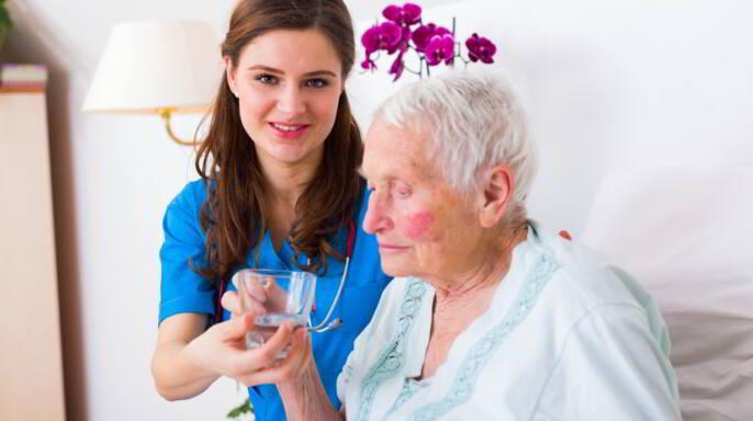 Enfermera cuidadora ayudando a anciana enferma