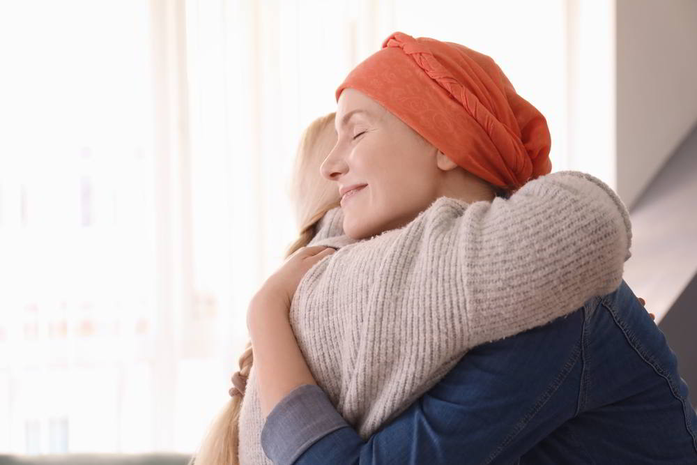 Mujer joven con cáncer abrazando a su madre en el interior