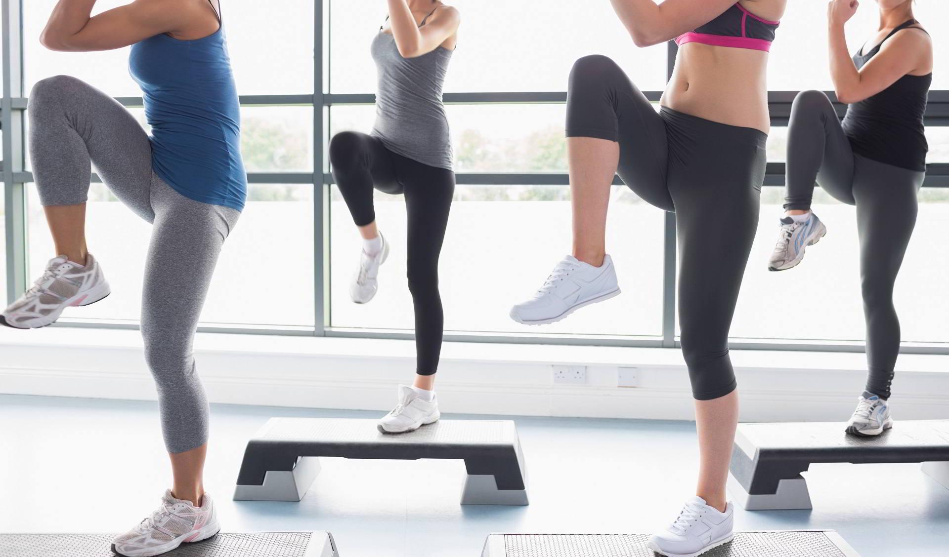Mujeres subiendo un paso y leventando las piernas como parte de un ejercicio