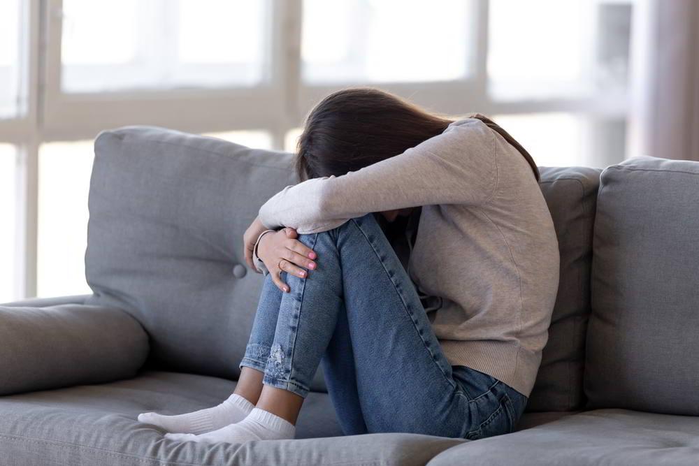 Deprimida chica adolescente sentada en el sofá sintiéndose ansiosa y sola