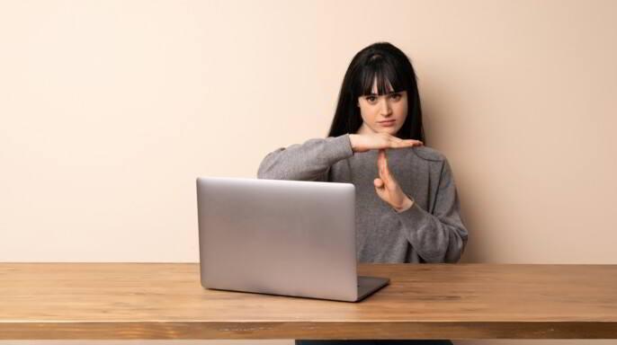 Mujer joven que trabaja con su computadora portátil haciendo con sus manos señal