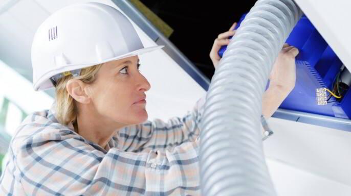 Trabajadora de instalación de sistema de ventilación