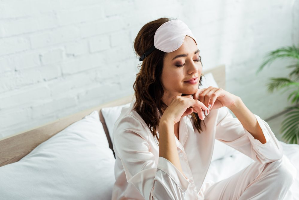 Atractiva mujer en la máscara de dormir con los ojos cerrados