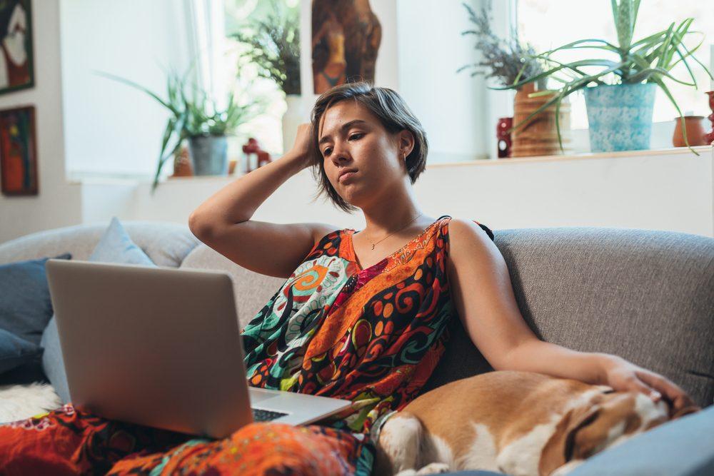 Mujer relajante en el sofá con perro usando el ordenador portátil