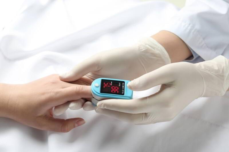 Doctora examinando paciente con oxímetro de pulso en la punta de los dedos
