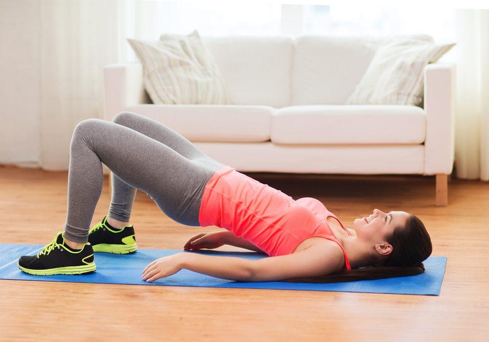 Chica sonriente haciendo ejercicio para piernas y nalgas