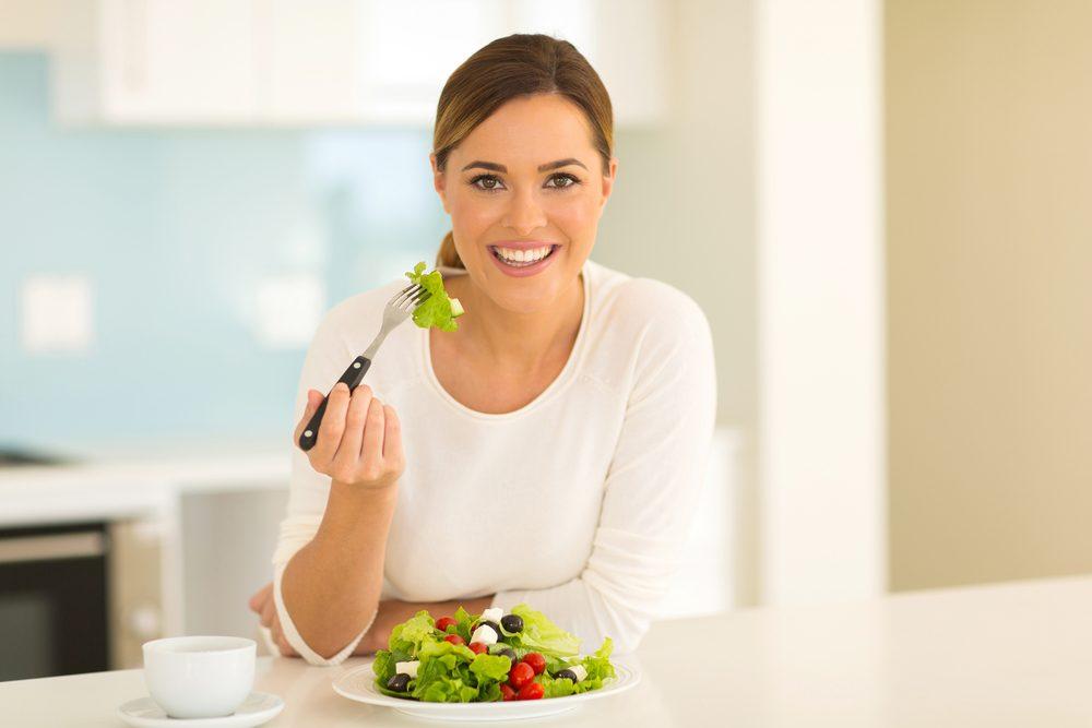 Mujer comiendo ensalada verde