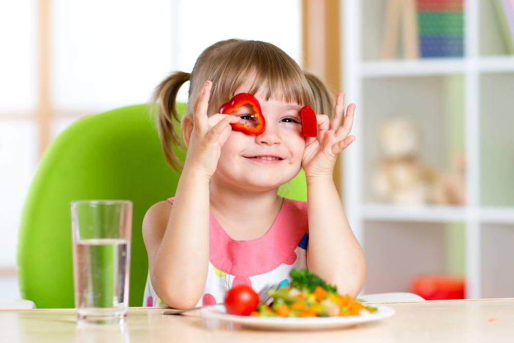 Niña divirtiéndose con verduras en la habitación de los niños