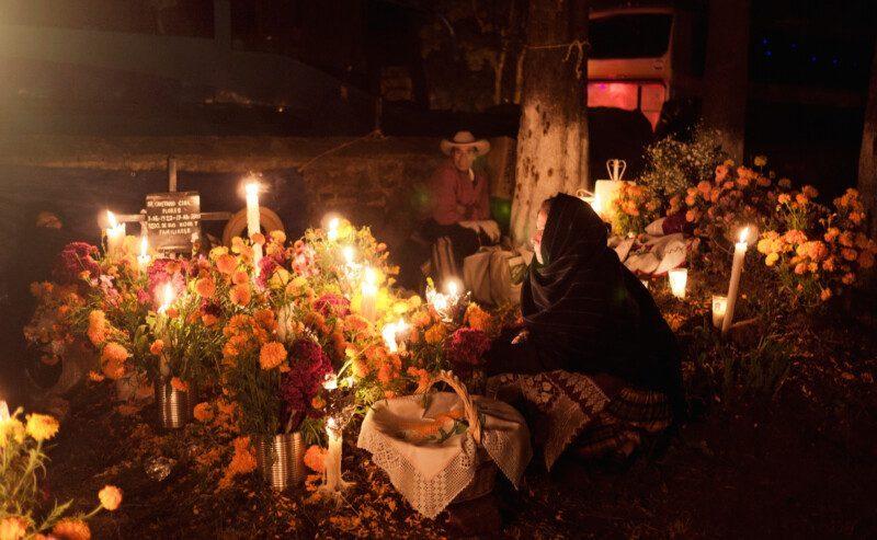 Mujer con ofrenda del día de muertos en un panteón