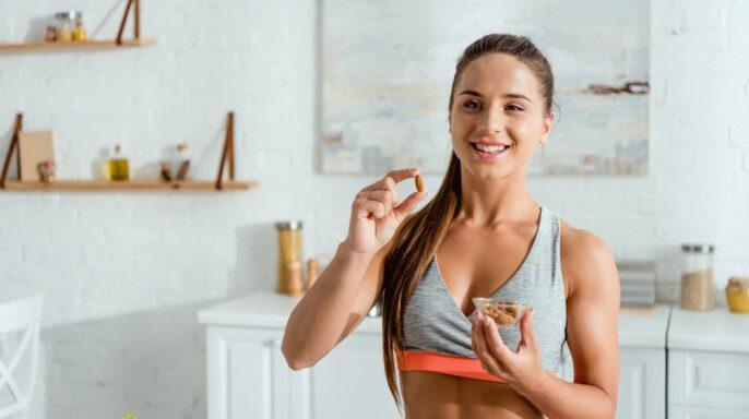 Mujer deportiva feliz sosteniendo almendra y sonriendo en casa