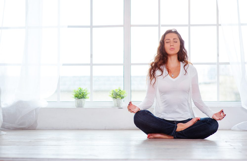 Mujer joven sentada en posición de loto