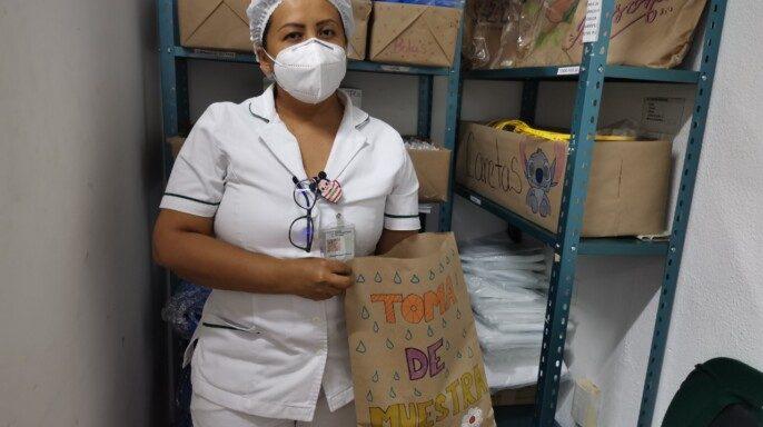 Juana y Laura, enfermeras de la Unidad de Medicina Familiar (UMF) No. 26 del Instituto Mexicano del Seguro Social (IMSS) en Acapulco, decoran y escriben frases motivacionales en los empaques de papel del Equipo de Protección Personal (EPP)